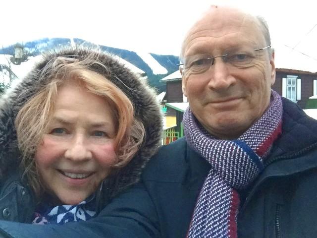 lächelnde Frau und lächelnder Mann in Winterkleudung vor Schneelandschaft
